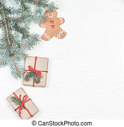 Christmas gifts, fir tree branches, xmas holiday decorations, festive symbols on white wooden background with copyspace. Christmas composition.
