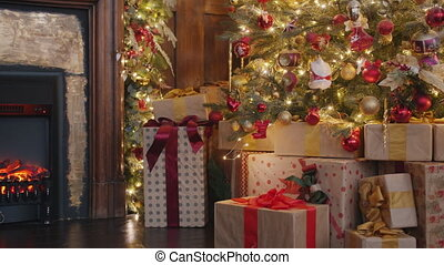 Christmas gifts under decorated tree in dark room illuminated with fire from fireplace, house is ready for traditional winter celebration. No people are visible.