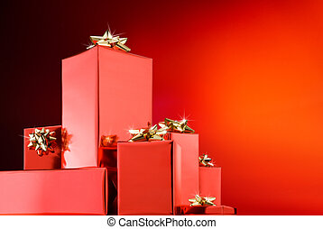 christmas gifts with golden ribbons over red background