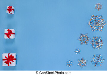 Christmas gifts with ribbon and snowflakes isolated on blue background. Concept of Christmas and new year.