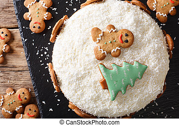 Christmas ginger cake with cheese cream is decorated with gingerbread close-up. horizontal top view
