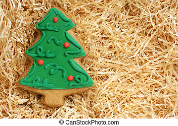 Christmas gingerbread cookie made in the shape of a Christmas tree on a paper shaving