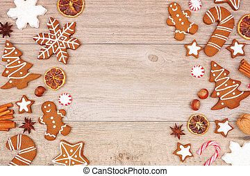 Christmas gingerbread cookies, candy and baking items, double side border on a wood background