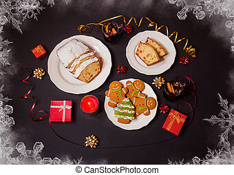 Christmas gingerbread cookies, christmas cake with candied fruits and raison, two glasses of mulled wine, burning candle and gifts on dark background. Top view.