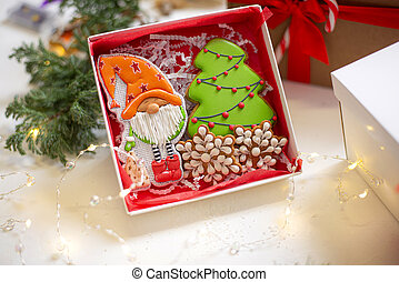 Christmas gingerbread cookies in the form of a festive gnome and a Christmas tree, Christmas decorations in the background. Close-up.