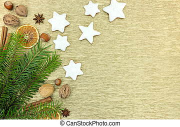 christmas gingerbread cookies with spices, nuts and fir tree branches on golden background