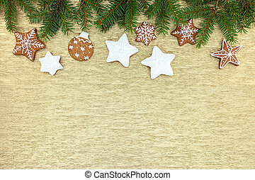 christmas gingerbread decorations with fir tree branches on golden background