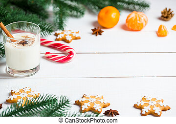Christmas Gingerbreads with glass milk and festive branches fir. Homemade delicious cookies on the wooden background. Free space for your text.