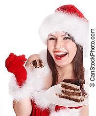 Christmas girl in Santa hat eat cake .