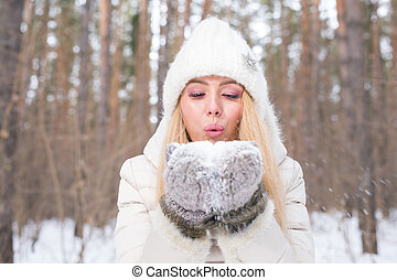 Christmas Girl. Winter young woman blowing snow in winter nature