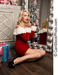 christmas girl with gifts sitting near mirror and paints lips with lipstick. woman dressed as Santa
