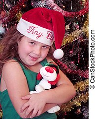 Christmas girl in santa hat holding stuffed animal in front of Christmas tree