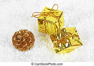 Christmas gold boxes and golden pine cone in the snow
