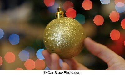 Christmas golden ball rotates at background bokeh