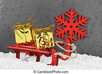 Christmas golden boxes on a red sled in the snow. Christmas greeting card.