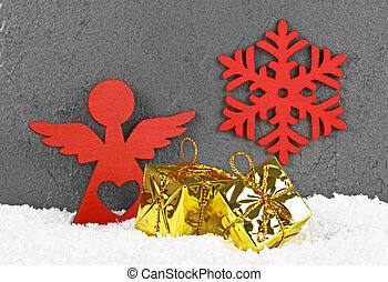 Christmas golden boxes, red angel and snowflake in the snow. Christmas greeting card.