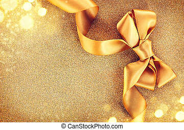 Christmas golden satin ribbon bow on a blinking holiday background
