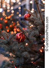 Christmas green pine tree with red glitter color balls on background bokeh light.