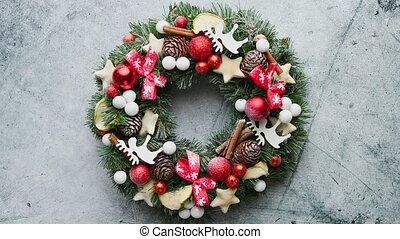 Christmas green, red and golden wreath with decorations isolated on stone background. Top view. New Year stylized composition