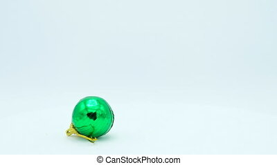 Christmas green shiny ball with golden handle rotating on white background.