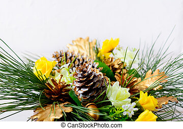 Christmas greenery with golden cones and yellow silk roses