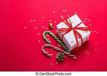 Christmas greeting card. Gift box and candy cane on red background