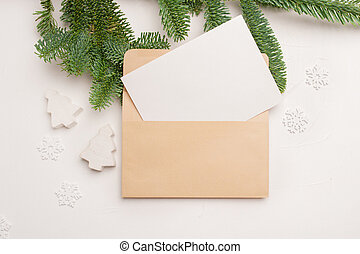 Christmas greeting card with envelope on wooden white background with fir tree branches and happy new year decorations. Top view copyspace