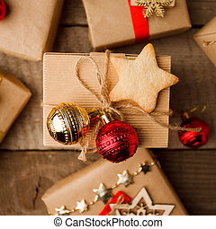 Christmas handmade gift box decorated with craft paper and red gold balls and handmade cookie star on vintage wooden background top view. Merry christmas greeting card. Winter xmas Happy New Year.
