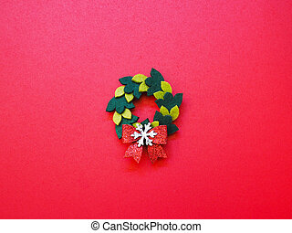 Christmas handmade wreat ornament on red background.
