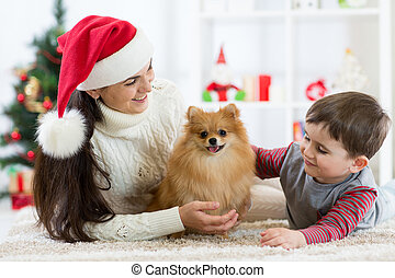 Christmas happy family of mother, her son child and dog spitz