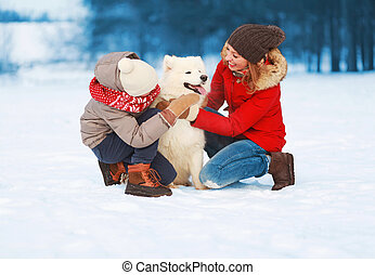 Christmas happy smiling family, mother and son child walking with white Samoyed dog on snow in winter day