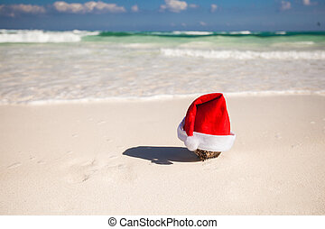 Christmas hat at coconut on a white sandy beach