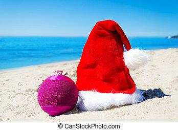 Christmas hat with christmas ball on the beach
