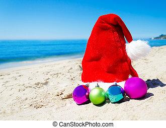Christmas hat with christmas balls on the beach