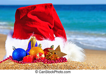 Christmas hat with colored baubles on the seashore