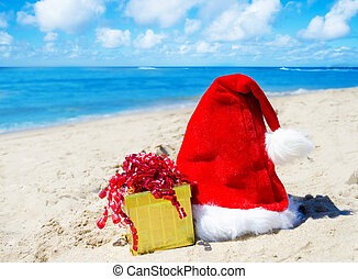 Christmas hat with gift box on the beach