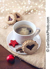 Christmas heart-shaped Cookie and coffee cup with red decoration.