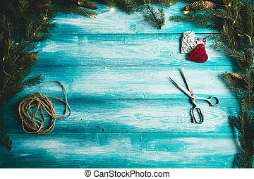 Christmas hearts on a blue wooden table with Christmas tree.