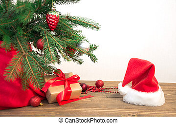 Christmas holiday background. Gifts with a red ribbon, Santa's hat and decor under a Christmas tree on a wooden board. Copy space on white.
