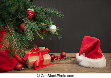 Christmas holiday background. Gifts with a red ribbon, Santa's hat and decor under a Christmas tree on a wooden board.