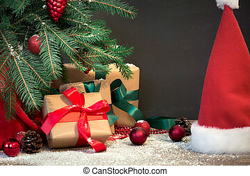 Christmas holiday background. Gifts with a red ribbon, Santa's hat and decor under a Christmas tree on a wooden board. Copy space on chalkboard.