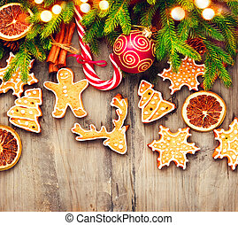 Christmas holiday border with gingerbread cookies, candy cane over wooden background