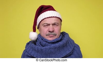 Christmas holiday concept. Displeased senior man in Santa Claus cap.