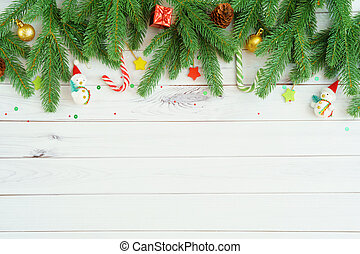 Green Fir tree branches with pine cones, lollipops, toy snowman's, gift box, gold ball on light wooden background.