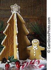 Christmas holiday gingerbread man and tree against dark wood rustic background. Vertical.