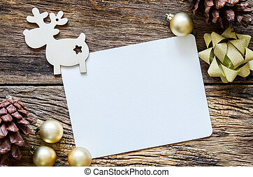 Greeting card for christmas with reindeer, decoration ball and fir on wooden table.