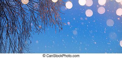 Christmas holidays lights on winter snowy sky background