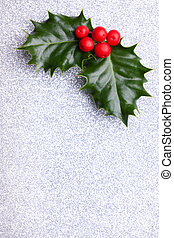 Christmas holly with red berries in the top of the corner on silver background