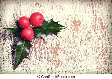 Christmas holly with red berries on wooden background