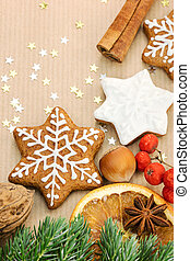 christmas homemade gingerbread cookies, spices and nuts on wrapping paper background